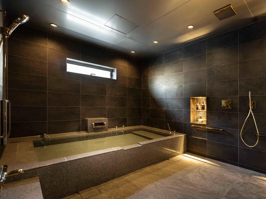 家族と足を伸ばして入る、大きな石貼り浴槽